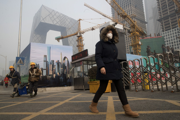 Image: A woman wearing a mask walks past a construction site as smog continues to choke Beijing