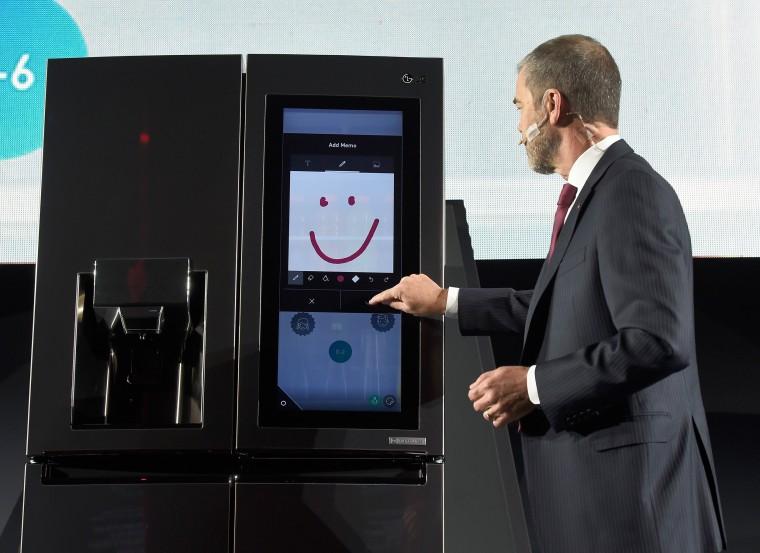 Image: An LG employee  demonstrates the LG Smart InstaView Door-in-Door refrigerato