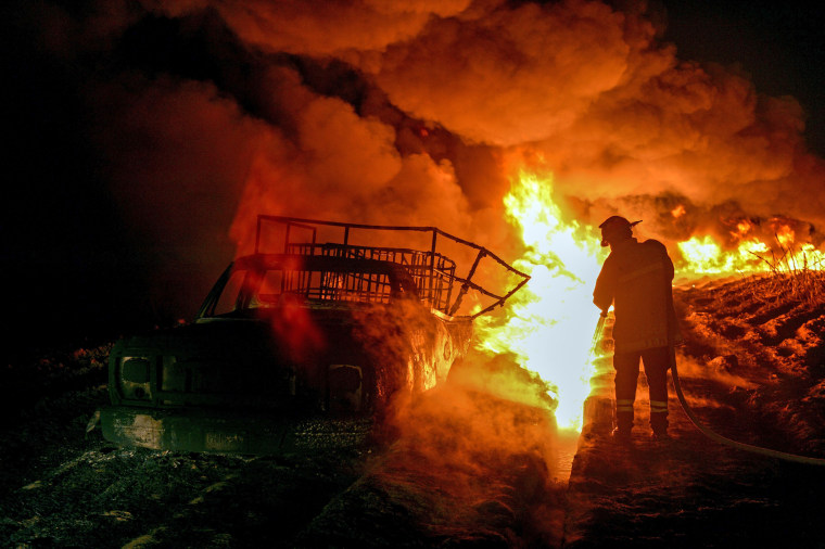 Image: Firefighters work to quell a fire on an alleged clandestine gasoline storage