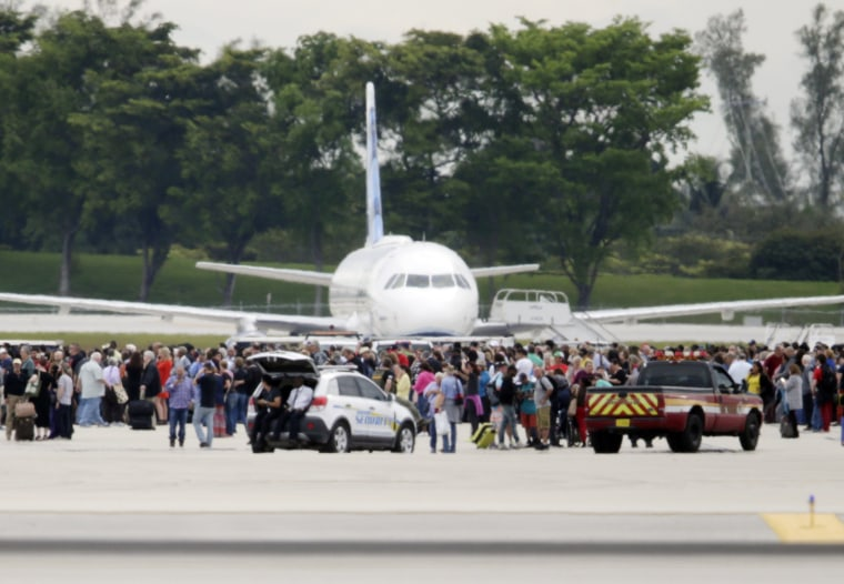Image: People stand on the tarmac at the Fort Lauderdale-Hollywood International Airport in Fort Lauderdale, Florida after a lone shooter opened fire inside the terminal on Jan. 6.