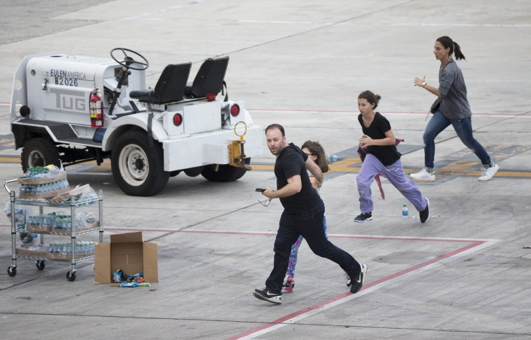 Image: People run on the tarmac at Fort Lauderdale-Hollywood International Airport on Jan. 6.