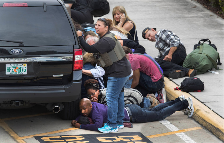 Image: People take cover at the Ft. Lauderdale Airport after a gunman opened fire on Jan. 6.