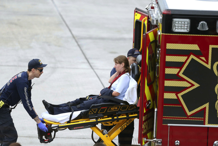 Image: An injured woman is loaded into an emergency vehicle at Fort Lauderdale-Hollywood International Airport after a gunman opened fire inside a terminal of the airport on Jan. 6.