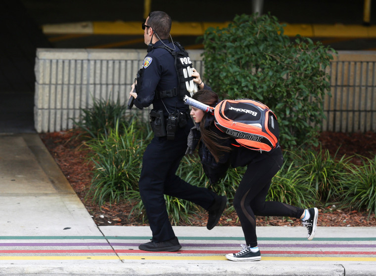 Image: A young woman runs behind a police officer as they seek cover outside of Fort Lauderdale-Hollywood International airport on Jan. 6.