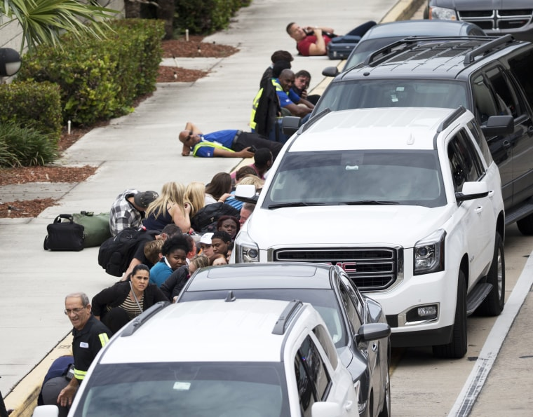 Image: People take cover outside Fort Lauderdale-Hollywood International Airport on Jan. 6.