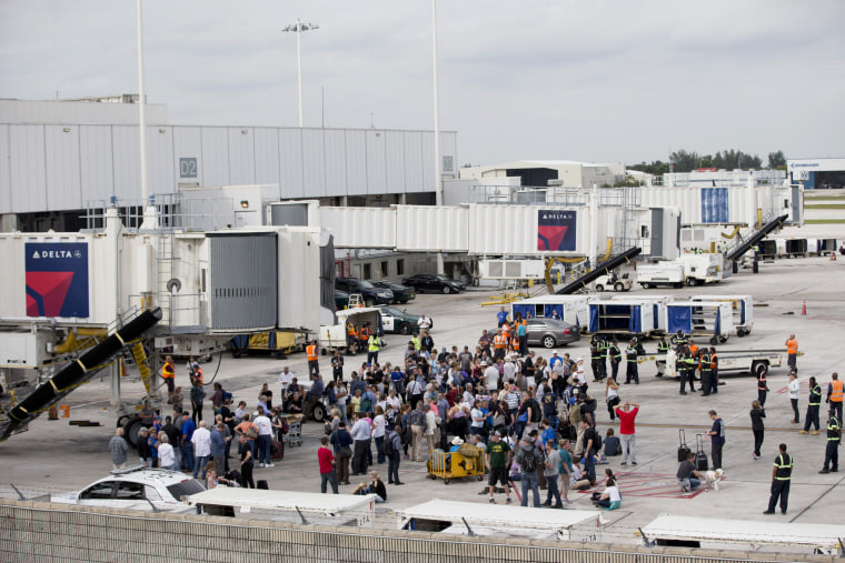Image: People stand on the tarmac at the Fort Lauderdale-Hollywood International Airport after a shooter opened fire inside a terminal of the airport on Jan. 6.