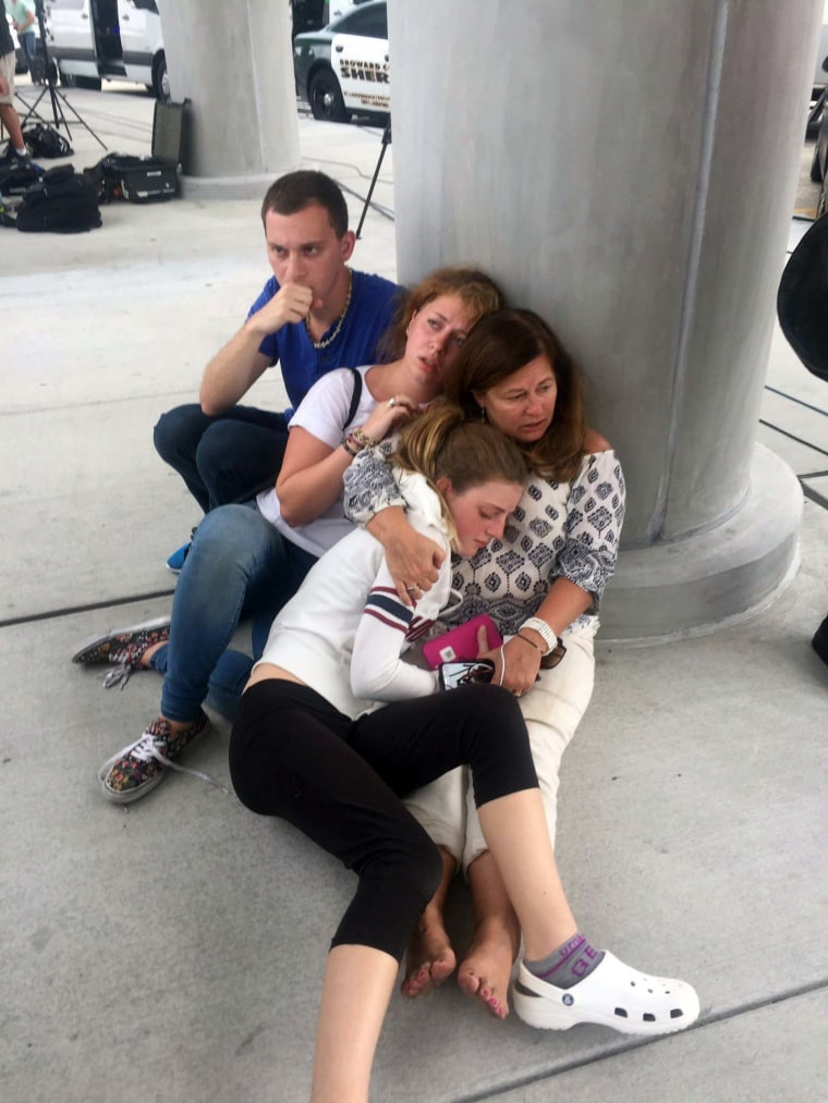 Image: People hide near a pole at Fort Lauderdale-Hollywood International Airport on Jan. 6.