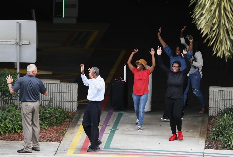 Image: People seeking cover walk towards police with their arms raised outside of Fort Lauderdale-Hollywood International airport after a shooting took place near the baggage claim on Jan. 6.