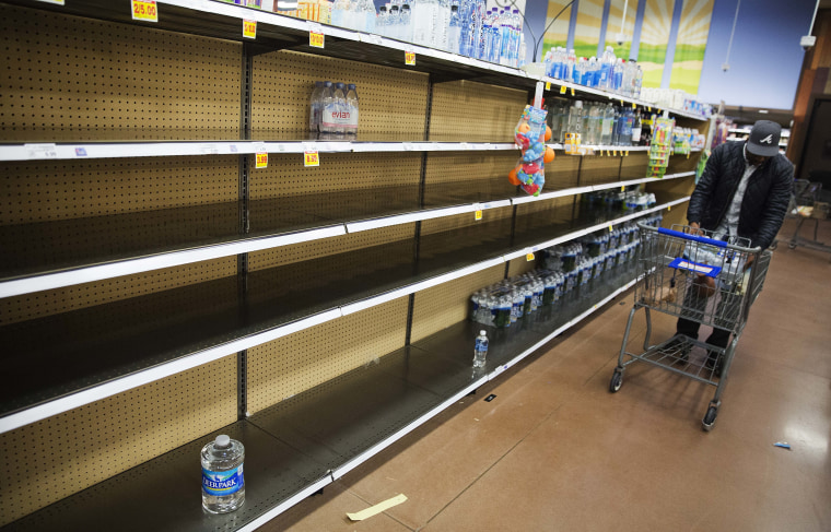 Image: Shelves of bottles of water sit mostly empty at a supermarket in Atlanta, Friday.