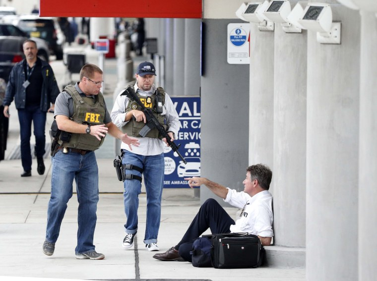 Image: Law enforcement officers talk to a man at Fort Lauderdale-Hollywood International Airport after the deadly shooting.