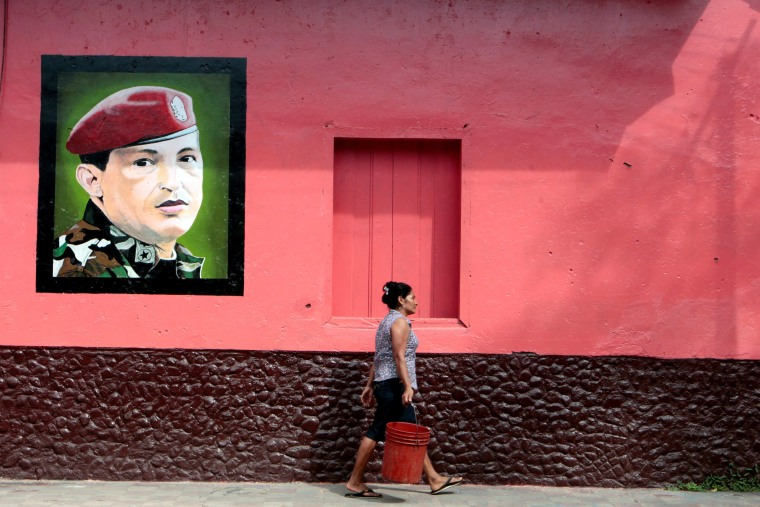Image: A woman walks past an image of late Venezuela's president Hugo Chavez in Altagracia town, Nicaragua
