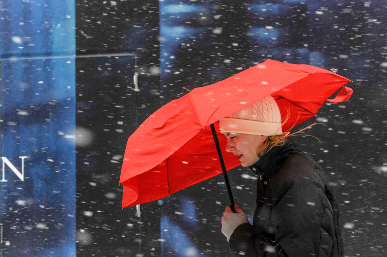 Image: A woman walks with a red umbrella during a snow storm in New York City