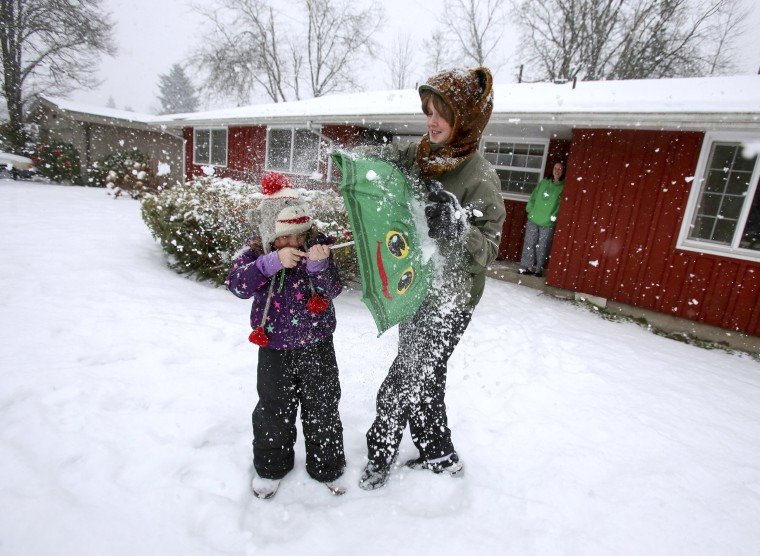 Image: Seven-year-old Juniper Jefferson (left) uses an umbrella to block a snowball from her brother, 13-year-old Aiden Jefferson, as the two played in the yard of their north Eugene, Oregon home on Jan. 7.