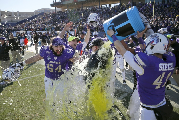 Image: James Madison's Matt Frank (64) and Brett Siegel (41) celebrate as head coach Mike Houston is dunked after their 28-14 win against Youngstown State in the FCS championship NCAA college football game, Jan. 7, in Frisco, Texas.