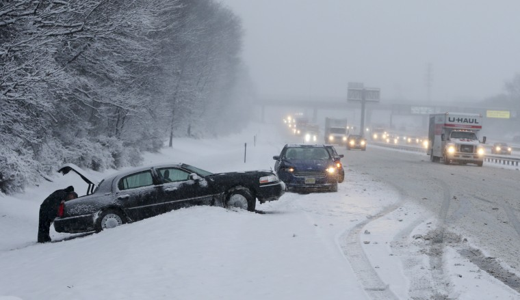 As traffic creeps past on the New Jersey Turnpike, drivers work on cars stuck in the snow Saturday, Jan. 7, 2017, near New Brunswick, N.J.