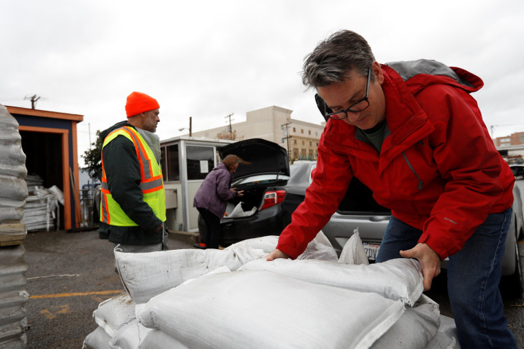 Image: People pick up sandbags from the Department of Public Works' Operation Yard in preparation of the incoming storm in San Francisco