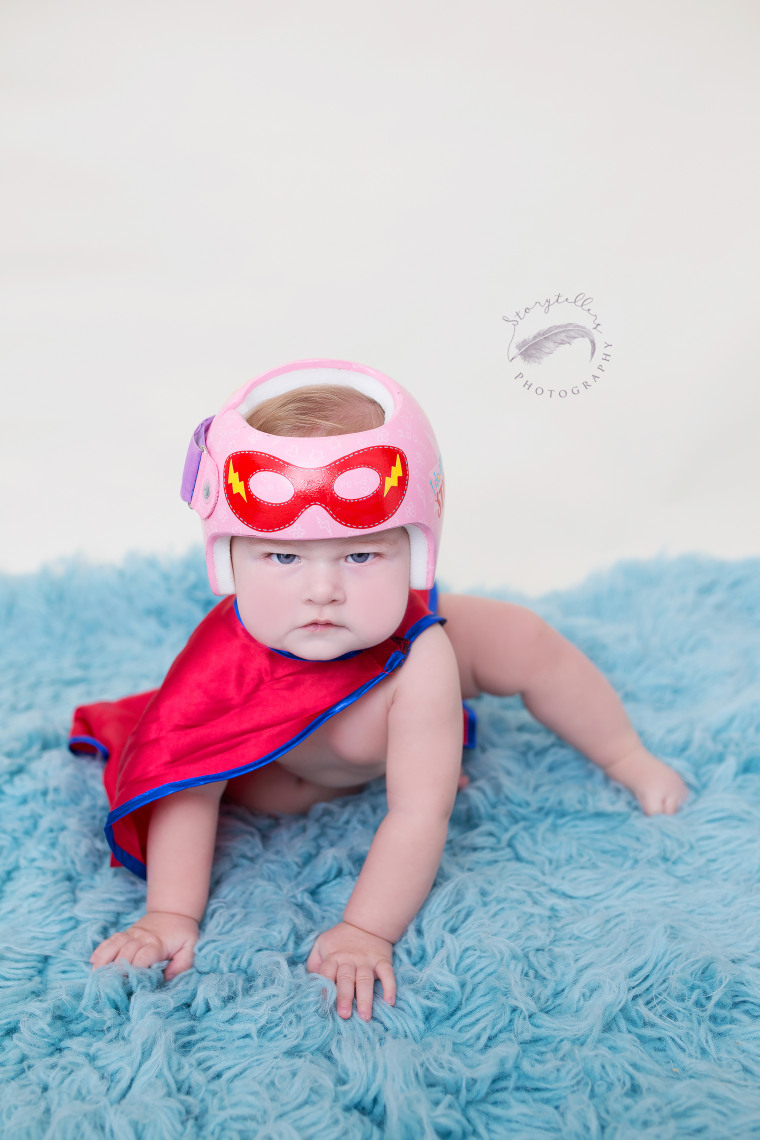 """Kaitlyn Smith says when she learned her daughter, Juniper, needed a helmet, she found herself captivated by Strawn's designs. """"The design we chose was a super hero theme and just kind of spilled out of my brain,"""" said Smith. """"The two quotes were chosen because they were funny, and represented the essence of Juniper."""""""