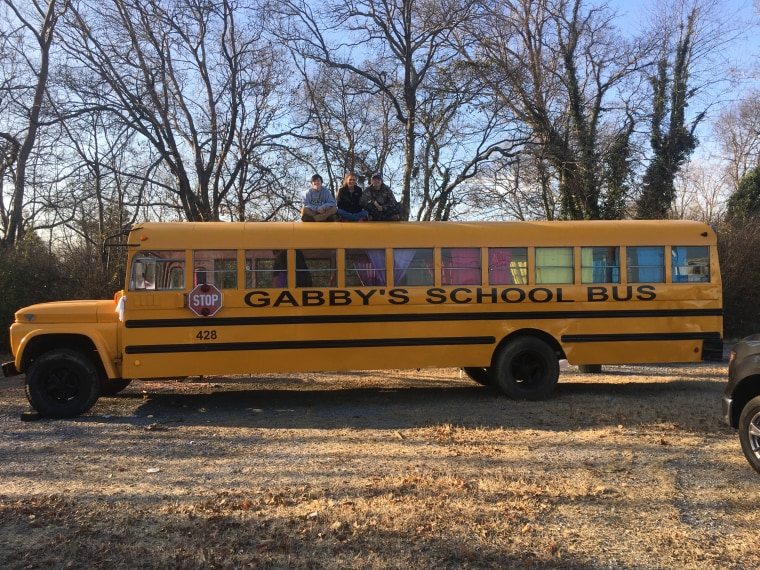 The restored bus. Jessi Smith, who organized the restoration efforts, sits on top between two friends who helped.