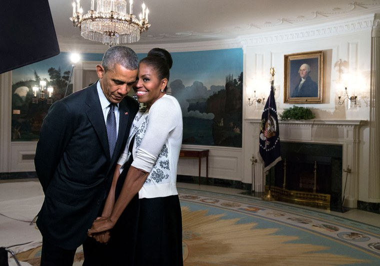 Michelle Obama snuggles against former president Barack Obama before a videotaping for the 2015 World Expo, in the Diplomatic Reception Room of the White House, March 27, 2015.