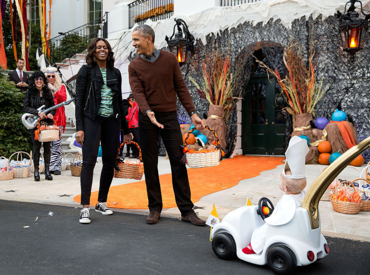 The president and first lady react to a child in a pope costume and mini popemobile as they welcomed children during a Halloween event on the South Lawn of the White House on Oct. 30, 2015.