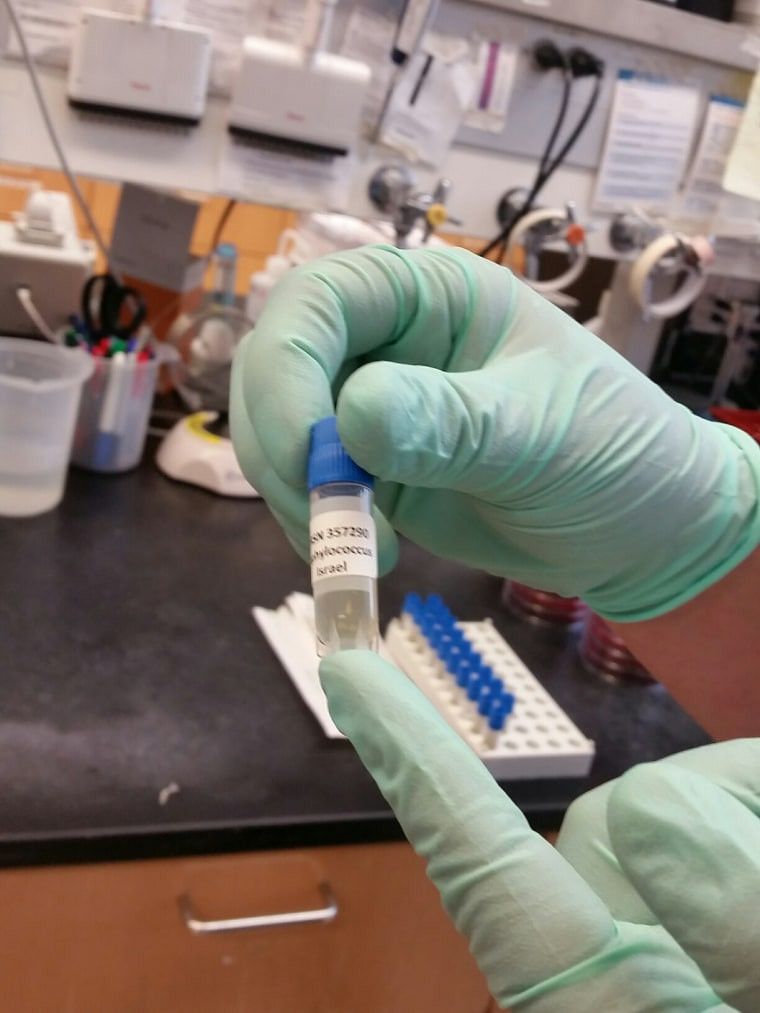 A researcher at Walter Reed Army Institute for Research holds a sample being tested for superbugs. A Nevada woman died from a feared superbug infection in August/