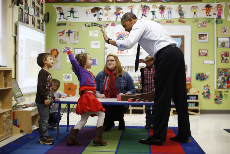 Image: U.S. President Barack Obama high-fives children in a pre-kindergarten classroom at College Heights early childhood learning center in Decatur