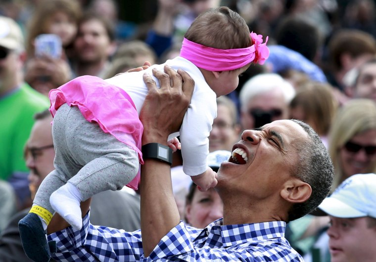 Image: President Barack Obama holds a baby during the 2016 White House Easter Egg Roll on the South Lawn