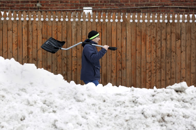 Image: A man walks with a shovel past a snow bank in the Elmhurst section of the Queens borough of New York.