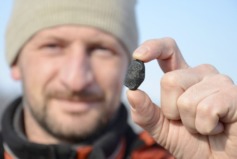 Image: A local resident shows a fragment thought to be part of a meteorite collected in a snow covered field in the Yetkulski region outside the Urals city of Chelyabinsk
