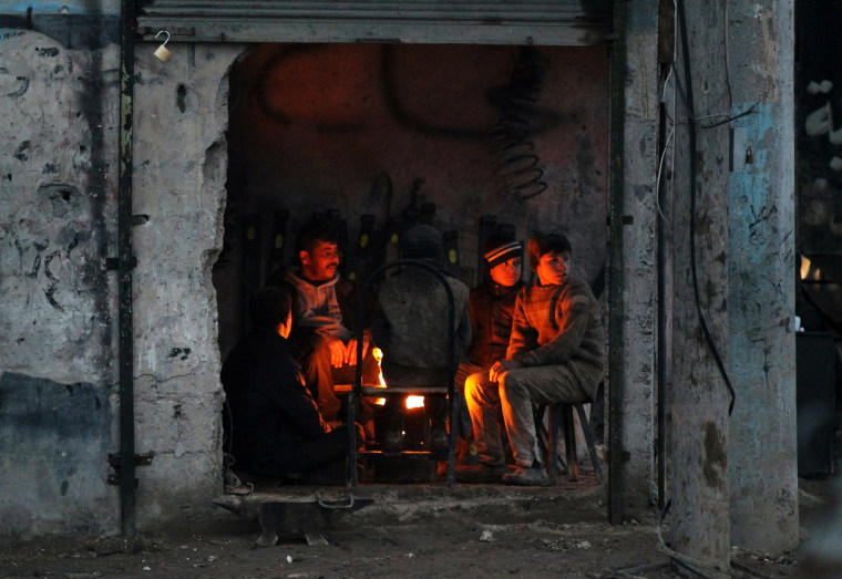 Image: People warm themselves around a fire inside a shop in the Syrian rebel-held town of al-Rai on Jan. 9.