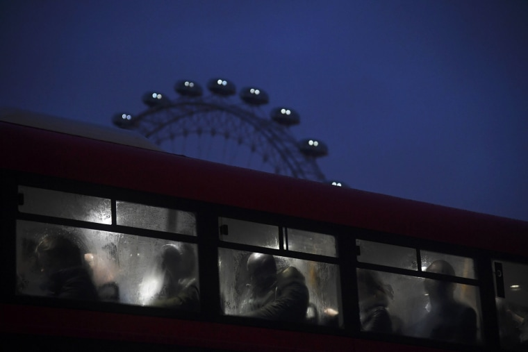 Image: Commuters ride a bus over Westminster Bridge past the London Eye during a strike on the Underground by members of two unions in protest of ticket office closures and reduced staffing levels on Jan. 9.
