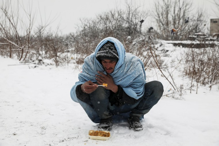 Image: A migrant eats free food during a snowfall outside a derelict customs warehouse in Belgrade, Serbia on Jan. 9.