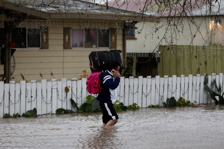 Image: File Photo: Cesar Belvasco walks through a flooded road while carrying his belongings after his home was flooded by the overflowing Petaluma River during a winter storm in Petaluma