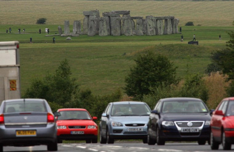 Image: Cars drive past Stonehenge on the busy A303 trunk road which passes within yards of the ancient monument at Stonehenge