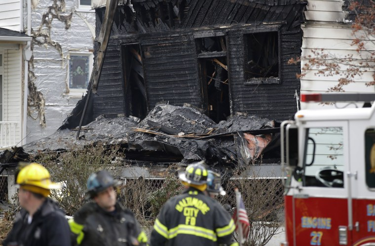 Debris from an early morning house fire is seen past fire officials in Baltimore, Thursday, Jan. 12.