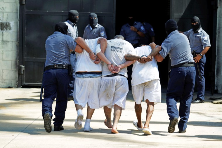 Mara Salvatrucha (MS-13) gang members are escorted upon their arrival at the maximum security jail in Zacatecoluca