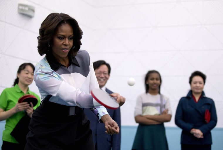 Image: U.S. first lady Michelle Obama plays table tennis during her visit of Beijing Normal School