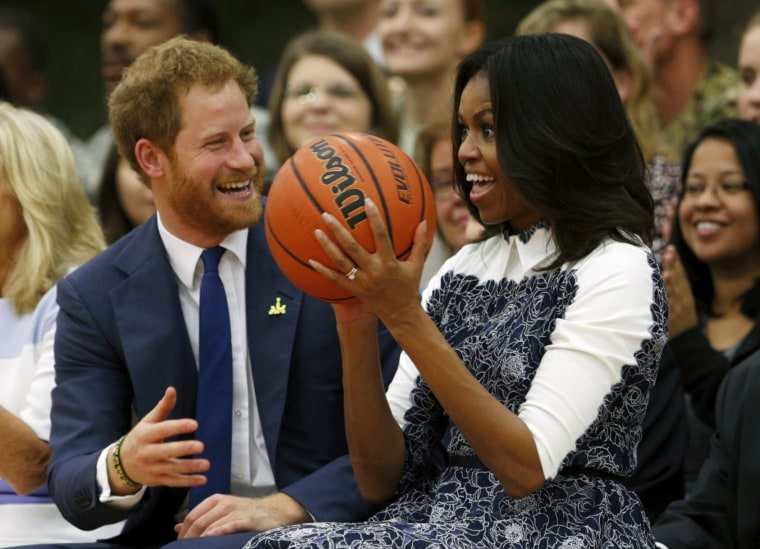 Image: Britain's Prince Harry laughs as U.S. first lady Michelle Obama catches a basketball during a game played by wounded warriors at Fort Belvoir, Virginia