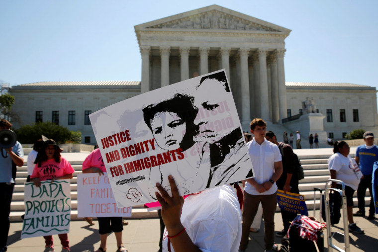 Image: Demonstrators from the immigrant community advocacy group CASA carry signs as they march in the hopes of a ruling in their favor on decisions at the Supreme Court building in Washington