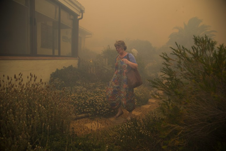 Image: A resident evacuates from her home as a fire spreads rapidly through residential areas in the mountainous suburb of Simonstown in Cape Town, South Africa, Jan. 11.