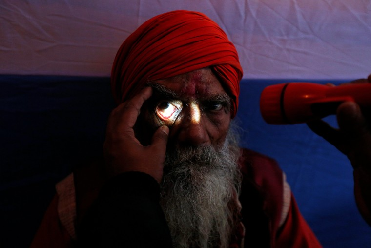 "Image: A Sadhu or a Hindu holy man undergoes an eye examination at a free eye-care camp organized by social workers at a makeshift shelter, before heading for an annual trip to Sagar Island for the one-day festival of ""Makar Sankranti"", in Kolkata, India."