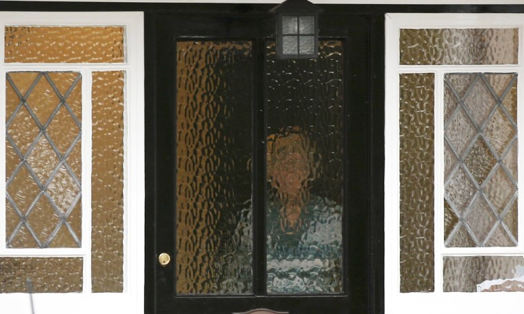 Image: A person stands behind textured glass at an address which has been linked by local media to former British intelligence officer Christopher Steele, who has been named as the author of an intelligence dossier on President-elect Donald Trump.