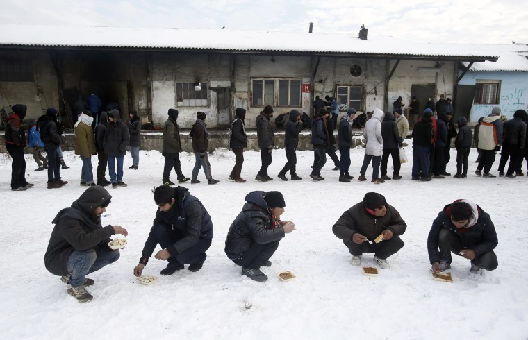 Image: Five migrants squat in the snow as they eat a warm meal distributed by aid groups as others queue for their portion outside a crumbling warehouse that has served as a makeshift shelter in Belgrade, Serbia, Jan. 12.