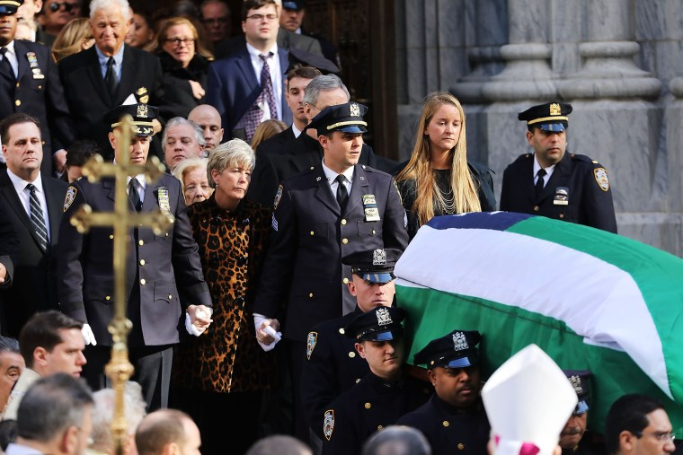 Image: Patricia Ann Norris-McDonald, wife of Detective Steven McDonald, and their son Conor follow McDonald's casket at St. Patrick's Cathedral during his funeral on Jan. 13 in New York City.