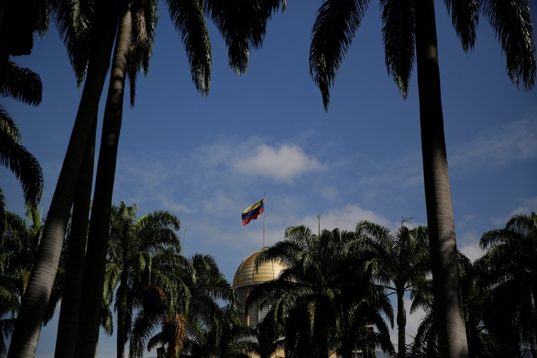 Image: The Venezuelan national flag is seen atop the building housing the National Assembly in Caracas
