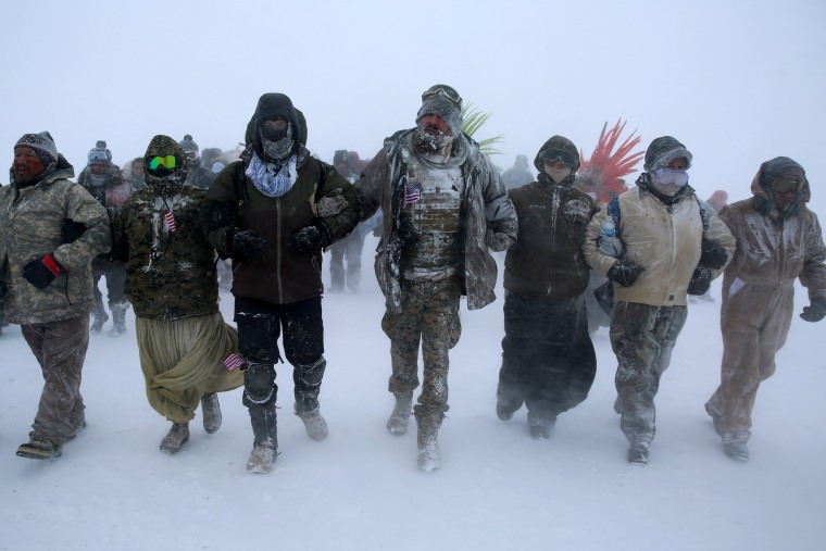 "Image: Activists march in protest with veterans outside the Oceti Sakowin camp where ""water protectors"" continue to demonstrate against plans to pass the Dakota Access pipeline adjacent to the Standing Rock Indian Reservation, near Cannon Ball, North Dako"