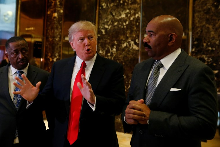 Image: U.S.President-elect Donald Trump speaks to members of the news media with television personality Steve Harvey (R) and businessman Greg Calhoun after their meeting at Trump Tower in New York