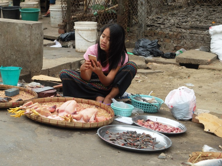 Image: A young woman selling chicken on a street uses a smartphone in downtown Yangon