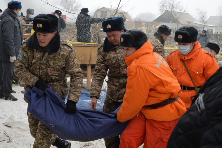 Image: Kyrgyz servicemen and rescuers carry a body bag with a victim of the crash.