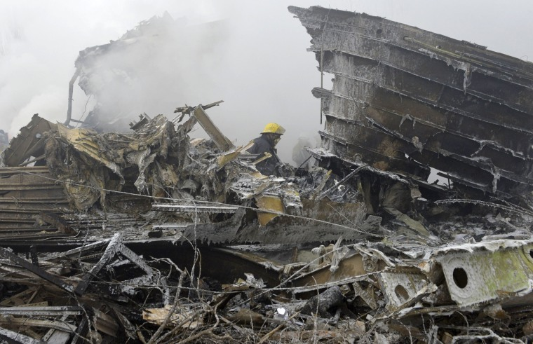 Image: Firefighters work among the remains of the crashed Turkish Boeing 747 cargo plane at a residential area.